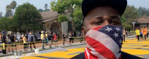 Justin wears an American flag a mask and stands in front of BLM mural